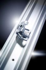 Die Rückwandhalterung im Vertikalprofil verfügt über ein Kontaktelement in Form einer Kralle. Beim Verschrauben der Rückwand mit dem Rahmenprofil wird ein leitender Kontakt hergestellt.