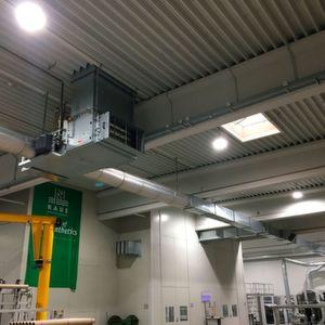 Der unter der Decke installierte Warmlufterzeuger saugt die aus der Halle aufsteigende Abwärme von Maschinen ebenso an wie etwa die durch Beleuchtung oder Sonneneinstrahlung entstehende Wärme und filtert diese.