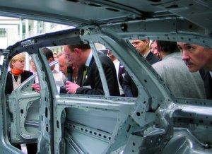 Thomas Schrödter (Mitte, mit Mikrofon), Teamleiter Produktionsplanung bei Mercedes-Benz, erläutert an der Karosserie des C-Klasse-Combi die praktische Realisierung einzelner Komponenten. Bild: Munde