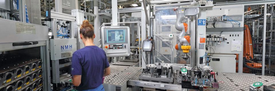 Die Anlage musste sich räumlich in die Produktionslinie einfügen. Dafür entwickelte Kuka Systems eine Stahlbaukonstruktion in Form eines Galgens, an der ein feinfühliger Leichtbauroboter befestigt ist. Der LBR iiwa kann so hängend arbeiten und nimmt wenig Platz in Anspruch.