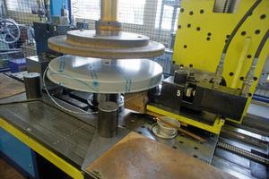 So entstehen die Waagschalen: Ein Werkstück ist zentral geklemmt und rotiert in der Maschine. Die ausgefransten Ränder des tiefgezogenen Blechteils werden geschnitten und gebördelt.