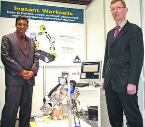 Abheek Kumar Bose, Roboteringenieur bei ADA (links), und Bernd Henning, Verkaufsleiter von ADA in Deutschland, vor dem Prototyp des Flexi-Bot-Handhabungssystems mit 1-kg-Roboter, Web-Kamera und Greifer. Bild: Kroh