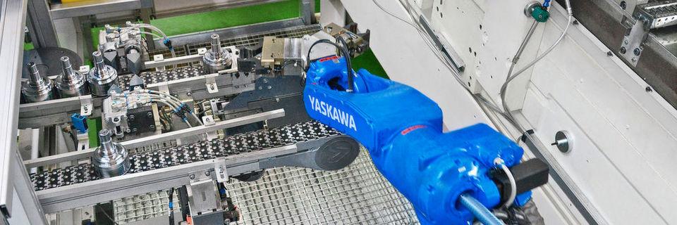 Der Motoman MH12 holt Rohteile am oberen Förderband ab und legt die bearbeiteten Fertigteile auf dem unteren Band wieder ab.