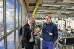 Durch eine dicke Glaswand getrennt sind Produktion und Testlabor (links) von den Ingenieursarbeitsplätzen. Betriebsleiter Igor Iraeta (r) erklärt Chefredakteur Frank Jablonski vom MM Deutschlanddie Abläufe.