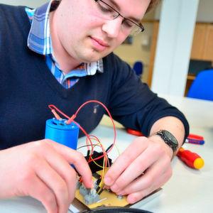 Mirko Demter überprüft die Verbindungen zur Ladeelektronik, die dafür sorgt, dass der Apparat eine gleichmäßige Spannung produziert, die dann angeschlossen ans Handy in Strom umgewandelt wird.