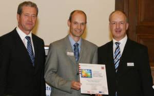 Das Netzwerk Automatisierungsregion erhält eine Auszeichnung: Erfolg beim 1. Hessischen Clusterwettbewerb. Richard Jordan von der IHK (mitte) und Jürgen Wrona (rechts), abcon, nehmen die Urkunde von Hessens Wirtschaftsminister Dr. Alois Riehl entgegen.