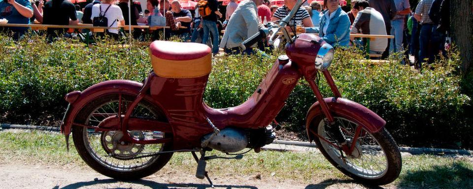 Der Fahrer dieses hierzulande recht seltenen, tschechischen Mopeds (Jawa 50 Pionyr, Baujahr 1958) genießt einen Ausflug zum Bockhorner Oldtimermarkt mit leckerem Erdbeerkuchen, reichlich Schlagsahne und dazu frisch gebrühten Kaffee.