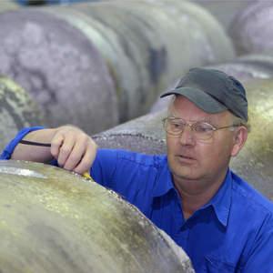 Ein Mitarbeiter der Thyssen-Krupp Titanium in Essen prüft die Oberfläche eines Titan-Blocks. Das Unternehmen wird zum 1. Oktober 2009 auf die Thyssen-Krupp VDM verschmolzen. Bild: Thyssen-Krupp Stainless