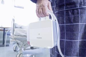 Patient mit Thopaz am Arm: Endlich Bewegungsfreiheit: Das nur ein Kilogramm leichte Gerät kann bequem der Ladestation entnommen und herum getragen werden.