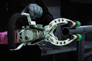 Die Schleifmaschine ist so konstruiert, dass eine Zweidrittelumschließung des Rohres möglich ist. Dafür sorgen die beiden beweglichen Greifarme, die über einen Hebel gesteuert werden. (Bild: Eisenblätter)