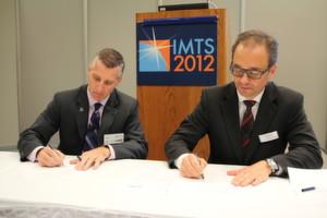 AMT-Geschäftsführer Doug Woods (links) und Deutsche-Messe-Geschäftsbereichsleiter Wolfgang Pech unterzeichnen ein Abkommen, um die Industrial Automation North America auch im Jahr 2014 parallel zur IMTS auszurichten.