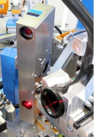 Detailansicht einer Laserprojektion auf den zu vermessenden Flansch und den danebenliegenden Sensorkopf der Gegenseite.