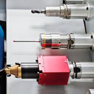 Bild 1: Blick in das Werkzeugmagazin der HSTM-Maschine: oben ein normales Fräswerkzeug, in der Mitte ein Messtaster und unten die Laserschweißeinheit mit rotem Grundkörper.