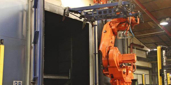 Bild 1: In der Strahlanlage befreit RHI seine stählernen Umlaufpaletten von Teerrückständen, die Handhabung übernimmt ein Roboter.