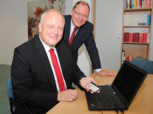 Elektronischer Personalausweis im Einsatz: Der Parlamentarische Staatssekretär Ulrich Kelber (l.) beantragt mit BfJ-Präsident Heinz-Josef Friehe das erste Führungszeugnis über das neue Internetportal.