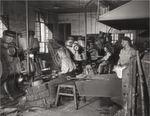 Die Aufnahme aus dem Jahr 1958 zeigt den Arbeitsalltag in der Schaufelschmiede. Die Arbeiter 'breiten' eine Schaufel mit einem damals modernen Presslufthammer.
