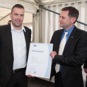 Die IHK Chemniz in Person von Michael Barth, Geschäftsführer der Regionalkammer Plauen, überreichte Geschäftsführer Titus Lehmann (l.) zum Jubiläum eine Ehrenurkunde.