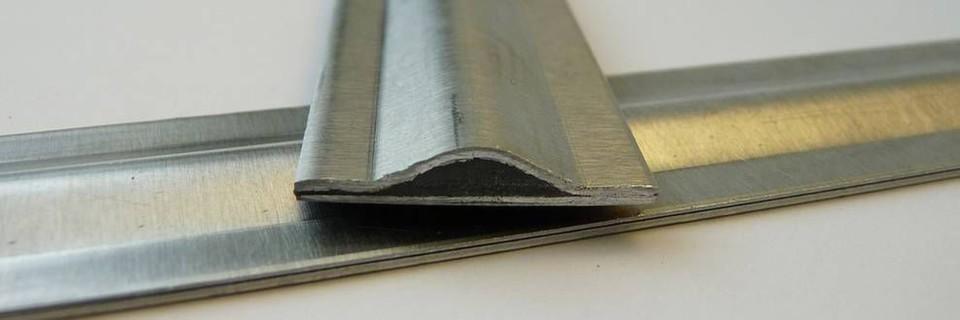 Ein Streifen aus dem neuartigen Blech-Schichtverbundwerkstoff im Querschnitt, der einseitig versickt ist. Die schwarze Füllung stellt Klebstoff dar, darunter liegt ein weiterer einseitig versickter Blechstreifen quer.