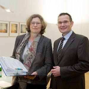 Regierungspräsidentin Anne Lütkes überreicht den Bescheid zum Betrieb der erweiterten Produktion an Hydro-Werkleiter Christoph Budde.