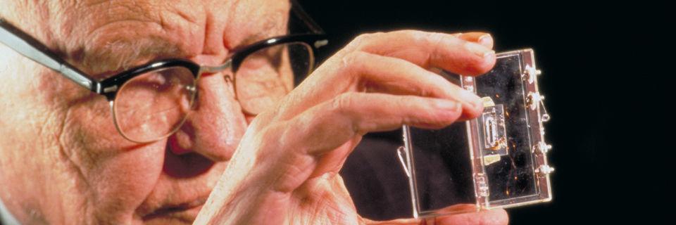 Der erste IC: Es war ein kleiner Baustein, den der Entwickler Jack Kilby 1959 in seinem Halbleiterlabor bei Texas Instruments einer kleinen Gruppe von Arbeitskollegen vorstellte. Auf einem Stück Germanium befanden sich ein Transistor, drei Widerstände und ein Kondensator.