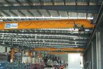 Die 22 m breiten Deckenkräne laufen auf Schienen, die die gesamte Hallenlänge überspannen; die Geschwindigkeiten und Rampenzeiten aller drei Kräne sind synchronisiert.