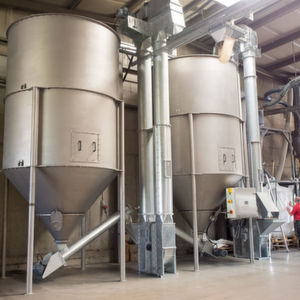 Die Materialzufuhr erfolgt mittels Sackaufgaben in einen Becherelevator mit Hochleistungsbechern. In Folge beschickt die Zuführschnecke die beiden Vertikalmischer über den Produkteinlauf im Deckel.