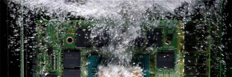 Das GreenICE-Kühlsystem: Die elektronischen Baugruppen befinden sich in einer speziellen Flüssigkeit, die schon bei moderaten Temperaturen verdampft. Der Phasenübergang von flüssig zu gasförmig maximiert den Kühleffekt.