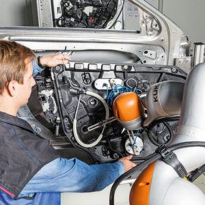 An der Montagestation kann der Roboter den Werker unter anderem bei einer Tätigkeit unterstützen.