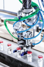 The F4 pick and place robot picks up one vial from the belt and pre-groups the vials on the Transmodul.