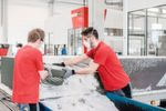 Employees unpack the molds from the VX4000 and remove excess sand.