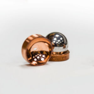 Copper mirrors direct and focus microwave photons in electrons on liquid helium system. The focusing mirror (on the left) is made by pressing a hard stainless steel ball (also shown in the picture) into a soft piece of copper. The flat mirror (on the right) shows two concentric circular electrodes (aka a Corbino pair) that are used to measure electron conductivity.
